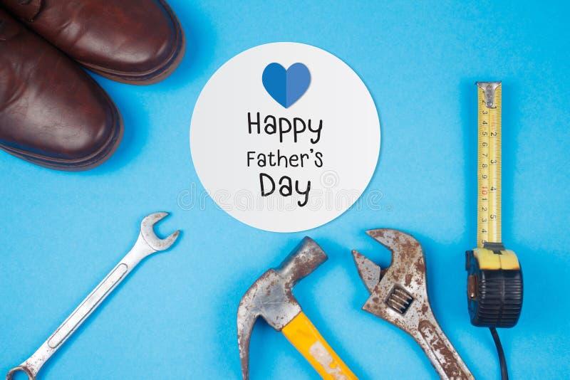 Texto feliz do dia de pai no cartão com as ferramentas oxidadas velhas e as sapatas de couro no fundo azul foto de stock