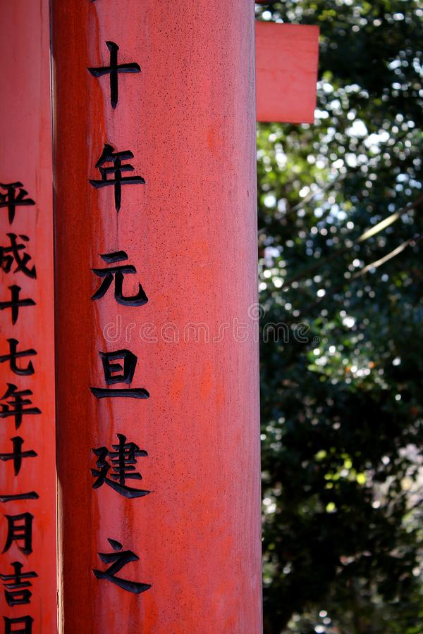 Texto japonês tradicional em cargos vermelhos da porta de Torii em Japão imagem de stock