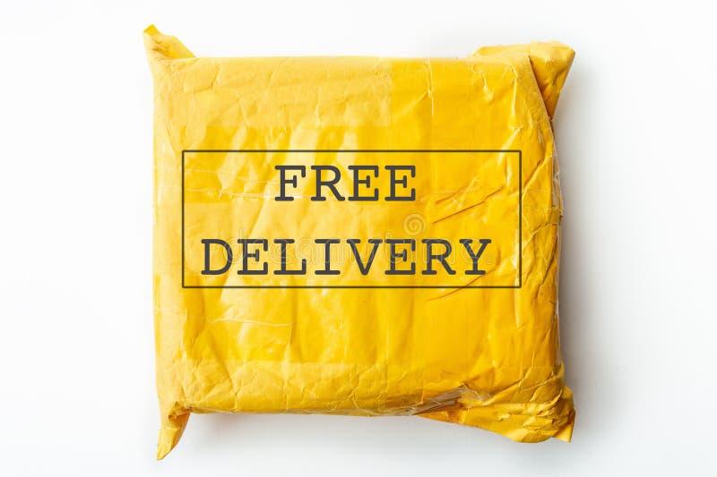 Texto LIVRE da ENTREGA no pacote do pacote ou na caixa amarela da carga com produto, transporte logístico livre e distribuição fotografia de stock