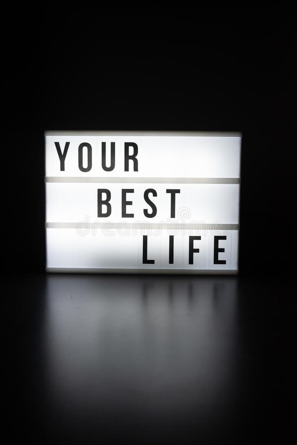 Texto no inglês que soletra sua melhor vida em um lightbox fotos de stock