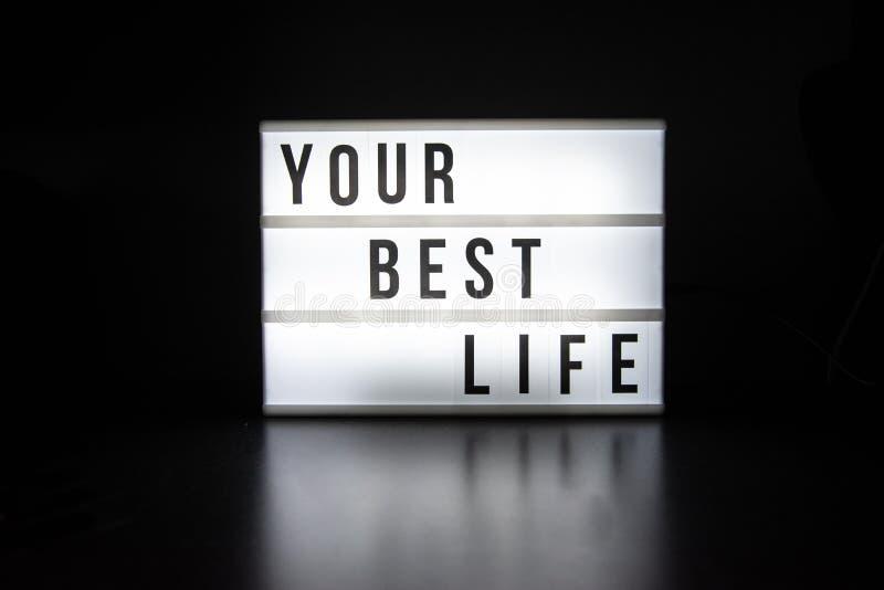 Texto no inglês que soletra sua melhor vida em um lightbox foto de stock