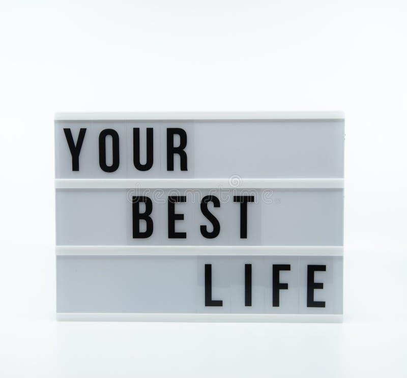 Texto no inglês que soletra sua melhor vida em um lightbox imagem de stock royalty free