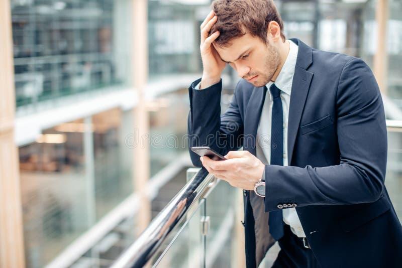 Texto novo preocupado de Read do homem de negócios no telefone celular fotografia de stock royalty free