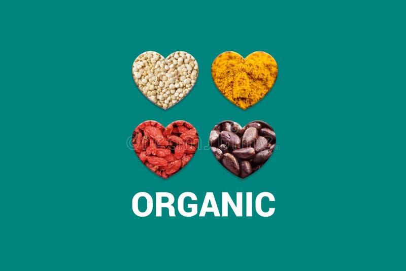 Texto orgánico blanco en fondo de la turquesa y cuatro corazones con las semillas del cacao, granos blancos de la quinoa, bayas s foto de archivo libre de regalías