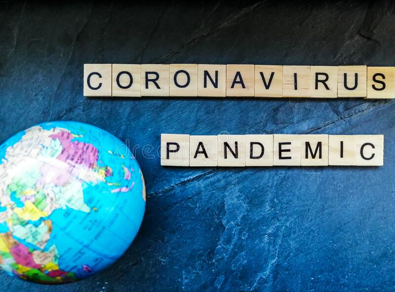 Texto pandêmico de coronavírus com o globo em fundo azul foto de stock