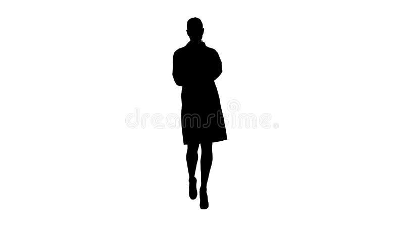 Texto que mecanografía del doctor lindo alegre de la mujer joven de la silueta en el teléfono mientras que camina foto de archivo