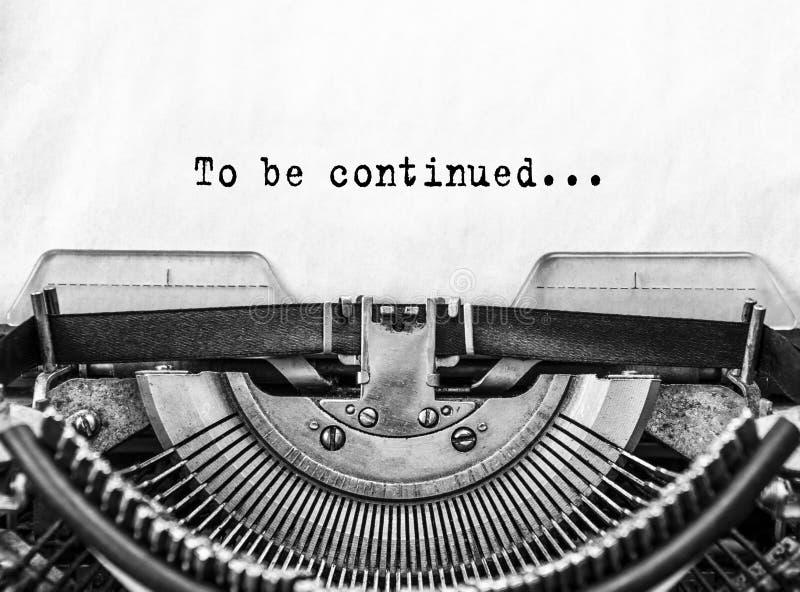 Texto que se continuará Palabras mecanografiadas en una máquina de escribir vieja del vintage imágenes de archivo libres de regalías