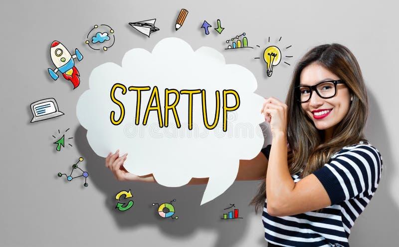 Texto Startup com a mulher que guarda uma bolha do discurso foto de stock royalty free
