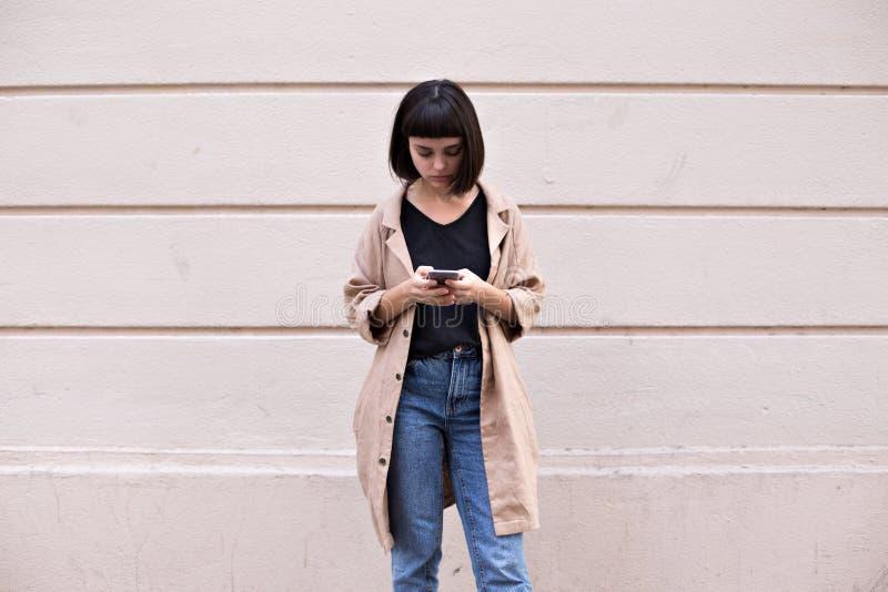 Textos de moda atractivos del adolescente en smartphone fotografía de archivo libre de regalías