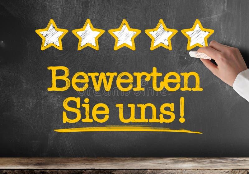 Textotez BEWERTEN SIE UNS, allemand pour le taux nous ou évaluez notre service, écrit sur le tableau noir avec cinq étoiles d'or illustration libre de droits