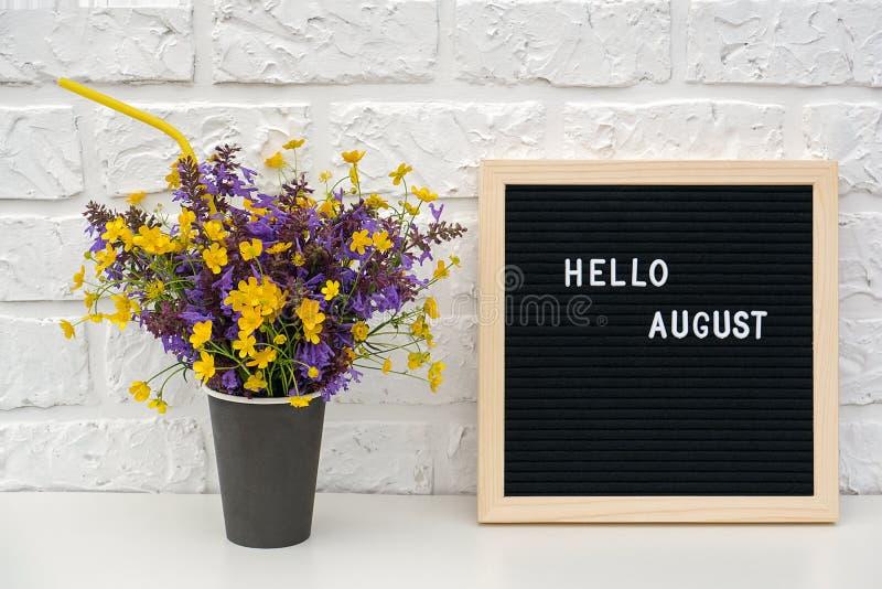 Textotez bonjour août sur le panneau de lettre noire et le bouquet des fleurs colorées dans la tasse de café de papier noire avec photo libre de droits