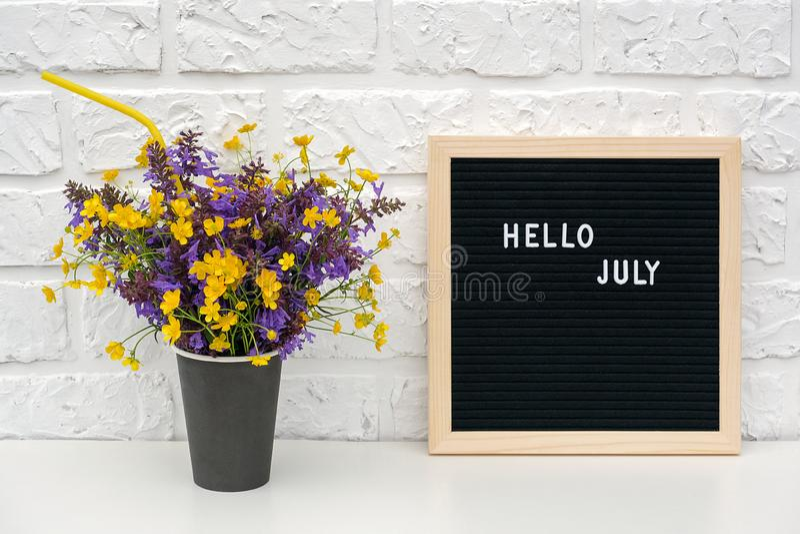 Textotez bonjour juillet sur le panneau de lettre noire et le bouquet des fleurs colorées dans la tasse de café de papier noire a images stock