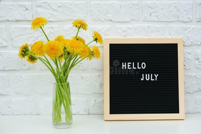 Textotez bonjour juillet sur le panneau de lettre noire et le bouquet des fleurs jaunes de pissenlits dans le vase sur le mur de  photo libre de droits