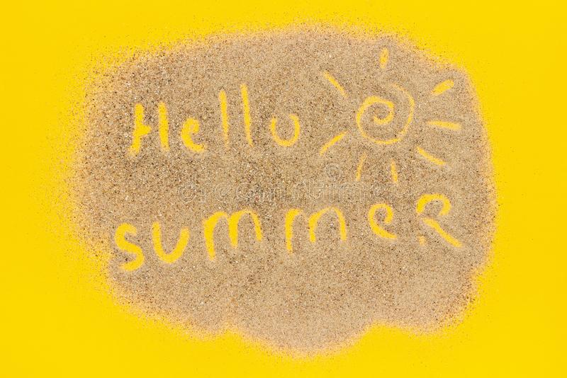 Textotez bonjour l'été et le signe du soleil dessinés sur le sable sur le fond de papier jaune Vacances créatives de concept de v image libre de droits