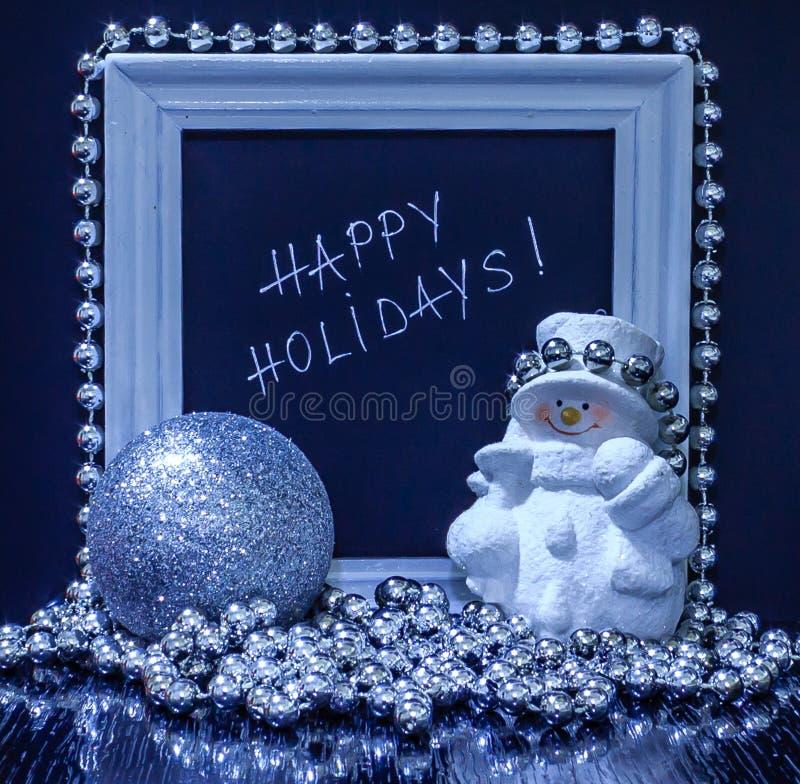 Textotez bonnes fêtes dans un cadre en bois blanc avec un bonhomme de neige, silv image stock