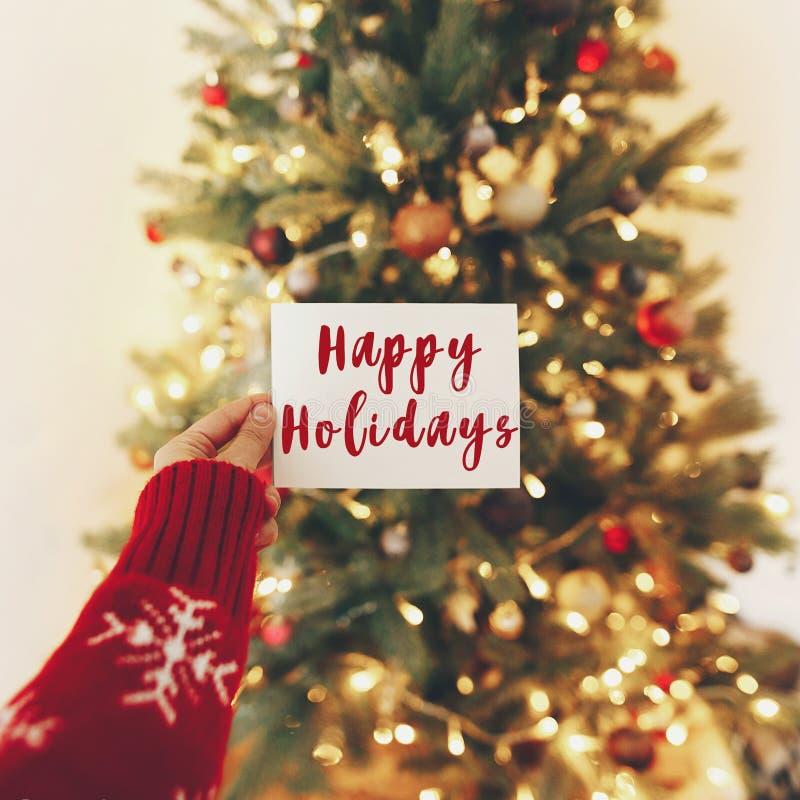 Textotez bonnes fêtes, les salutations de saisons, carte de main sur le fond photo stock