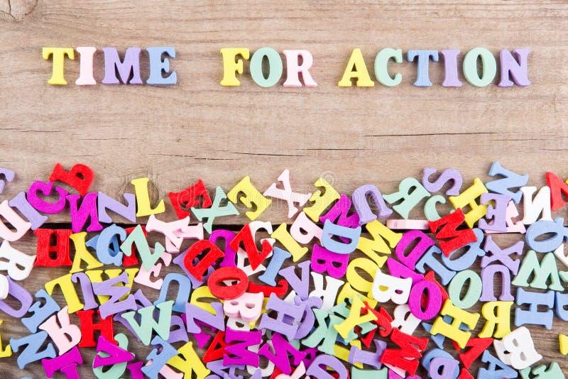 """Textotez la """"heure pour l'action """"des lettres en bois colorées images stock"""