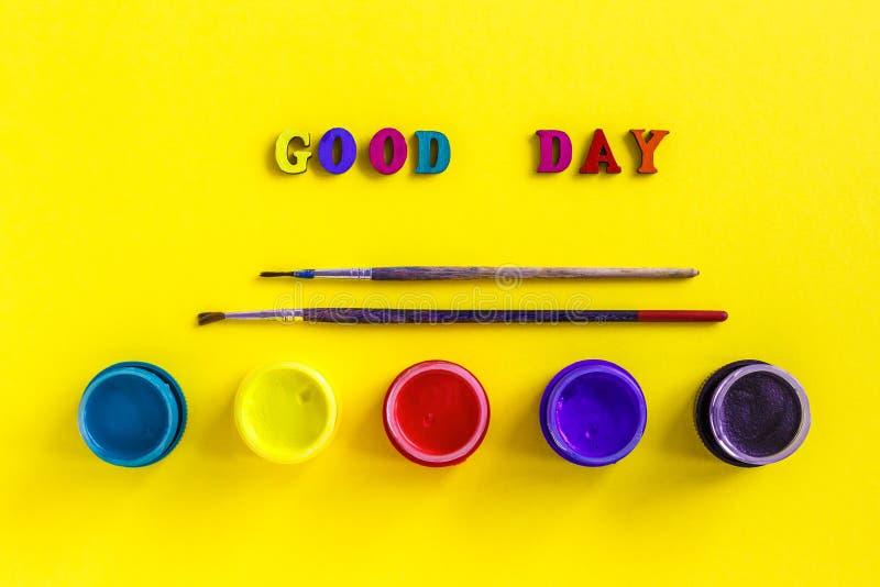 Textotez le beau jour, les pots avec la gouache et les pinceaux sur le dos de jaune photographie stock libre de droits