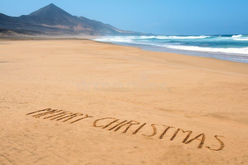 Textotez le Joyeux Noël dans le sable d'une plage photographie stock libre de droits