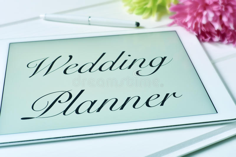 Textotez le planificateur de mariage dans l'écran d'un comprimé photographie stock libre de droits