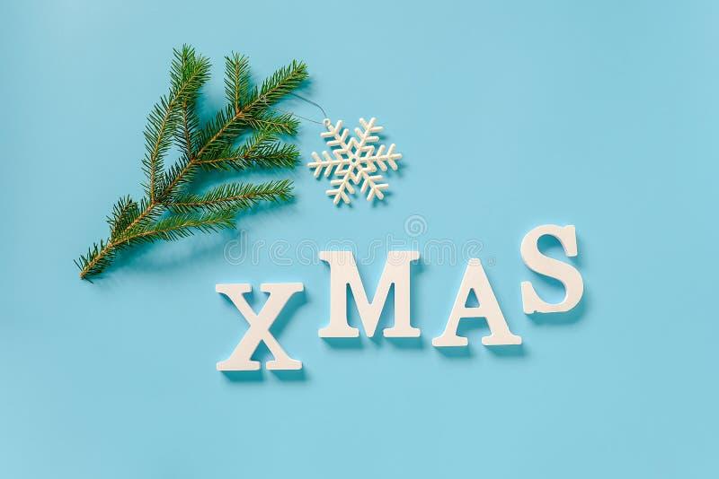 Textotez Noël des lettres et du jouet blancs de flocon de neige de décoration de Noël sur la branche impeccable, fond bleu Joyeux photo stock