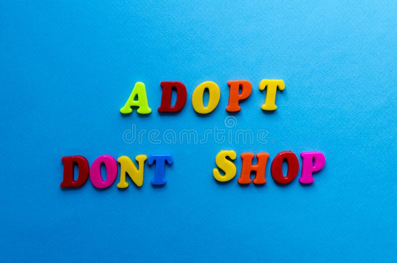 Textotez pour adopter ne font pas des emplettes des lettres colorées en plastique sur le fond de papier bleu images libres de droits