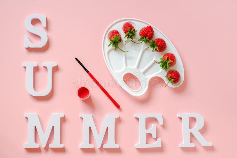 Textsommar, röda mogna jordgubbar på den konstnärliga paletten, borste och gouache på rosa bakgrund Idérik målarfärg för begrepps royaltyfria foton