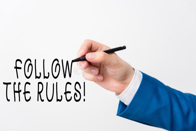 Texttecken som visar Följ reglerna Konceptuellt foto omfattas av regler för uppförande eller procedur Isolerad hand royaltyfri foto