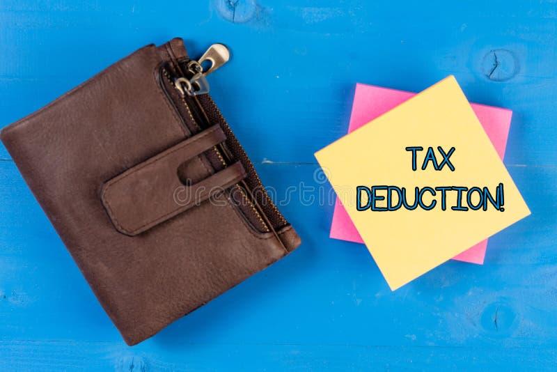 Texttecken som visar skattavdrag Det begreppsmässiga fotobeloppet som subtraheras från inkomst, innan det beräknar skatt, är skyl royaltyfria foton