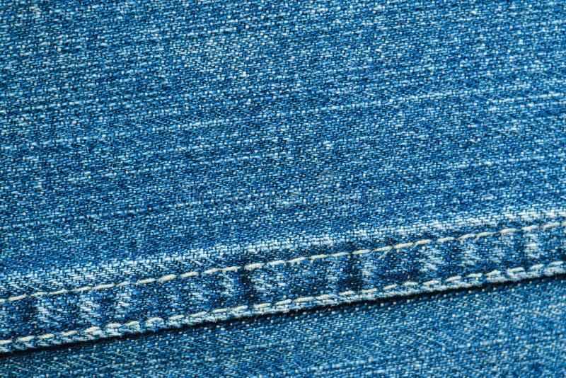 Textur av blått grov bomullstvillmaterial med en sömsnärbild arkivfoto