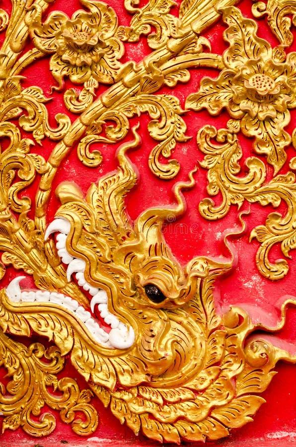 Textur av det guld- färgträdet för stuckatur på Wat Prathat Lampang Luang royaltyfria foton