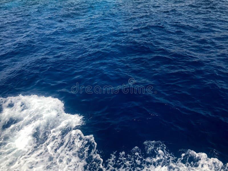 Textur av en bubblandeblått blöter havsvatten med vågor, bubblor, vitt skum, plaskar, färgstänk, droppar grönska för abstraktionb arkivfoton