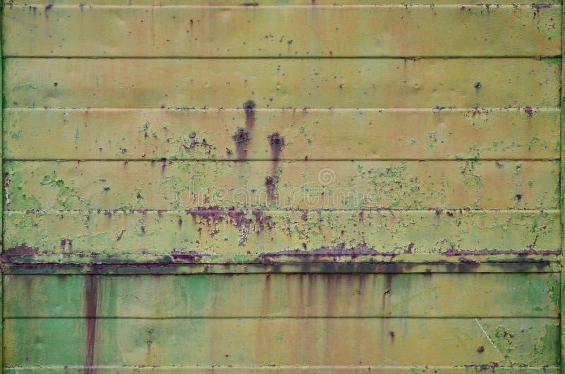 Textur av en gammal vägg för gul metall med viktig skada från exponering till ofördelaktiga vädervillkor och dampnes royaltyfri fotografi