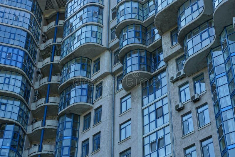 Textur av en grå vägg med blåa balkonger och fönster royaltyfria foton