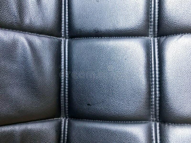 Textur av en lättnadsyttersida som göras av svart konstgjord och konstgjord läder för läder, med en modell av fyrkanter som sys m royaltyfria bilder