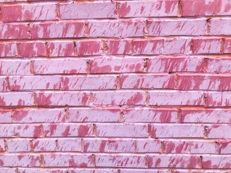 Textur av en mjuk gammal sprucken tegelstenvägg för härliga unika ovanliga rosa färger av rektangulära tegelstenar med sömmar som arkivbild