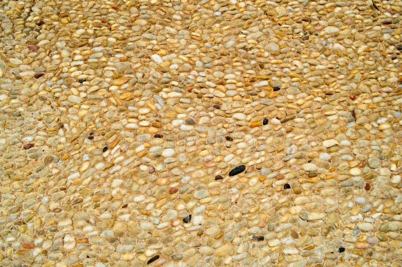 Textur av en stenvägg, vägar från liten runda och ovala stenar med sand med sömmar av naturlig gammal gulingsvart bryner Bakgrund arkivbilder