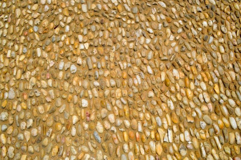 Textur av en stenvägg, vägar från liten runda och ovala stenar med sand med sömmar av naturlig gammal gulingsvart bryner Bakgrund royaltyfria foton