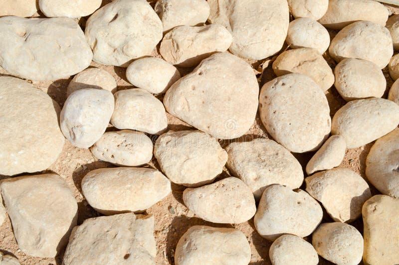 Textur av en stenvägg, vägar från stor runda och ovala stenar med sand med sömmar av naturlig gammal gulingsvart bryner Bakgrund royaltyfria bilder