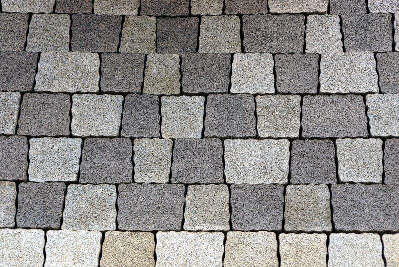 Textur av ett fragment av tegelplattor för grå färgfyrkantstenläggning på vägen royaltyfri bild