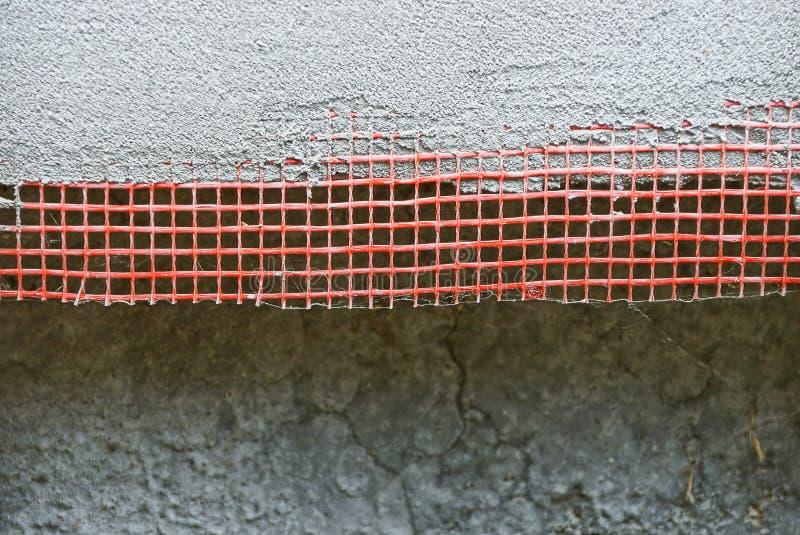 Textur av ett rött plast- ingrepp på en grå betongvägg royaltyfria bilder