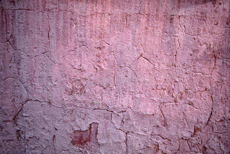 Textur av gammal rosa skalande målarfärg på väggen i sprickorna arkivbilder