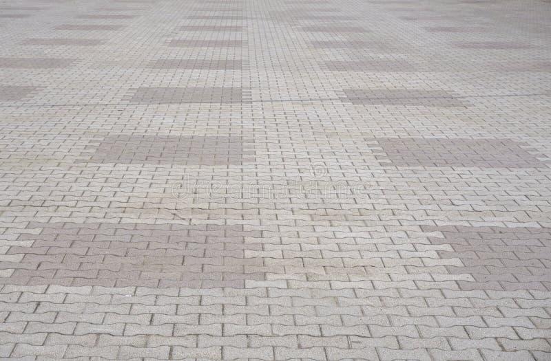 Textur av grå färger och guling mönstrade stenläggningtegelplattor på jordningen av gatan, perspektivsikt Kvadrerat stengolv för  royaltyfri fotografi