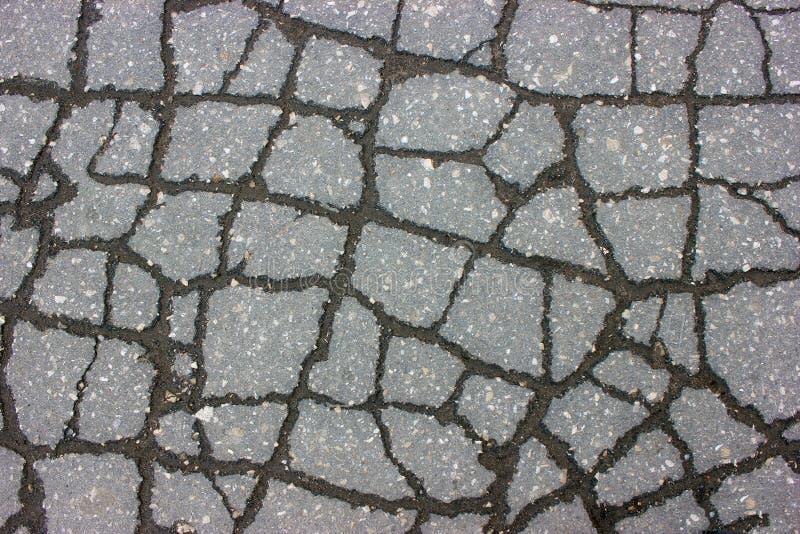 Textur av grov asfaltbeläggningvägen med sprickor - abstrakt bakgrund arkivbild