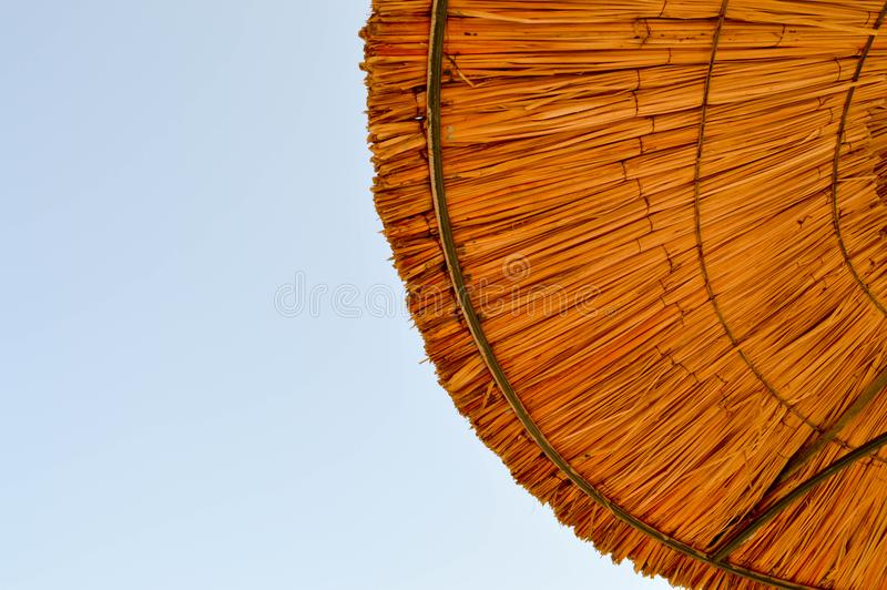 Textur av naturliga solparaplyer för härligt sugrör som göras från hö i en tropisk ökensemesterort som vilar mot arkivfoto