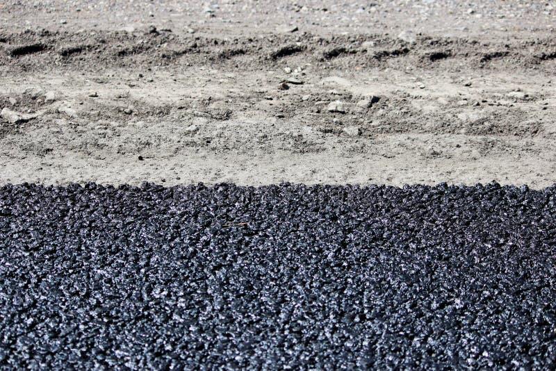 Textur av ny varm svart asfalt läggas på den nya vägen nära vägren- och bilspåret royaltyfri bild