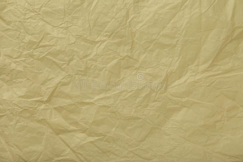 Textur av skrynkligt beige inpackningspapper, closeup Guld- gammal bakgrund arkivbild