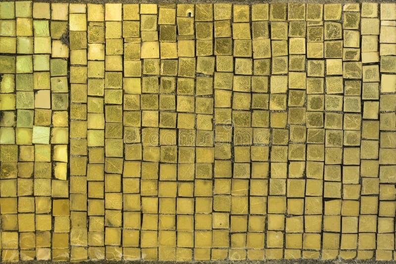 Textur av små fyrkanter av mosaiken i guld- gul keramisk tegelplatta arkivfoton