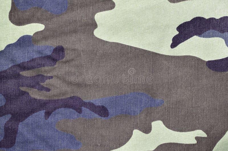 Textur av tyg med en kamouflage målade i färger av träsket Armébakgrundsbild Textilmodell av militär kamouflage royaltyfri fotografi