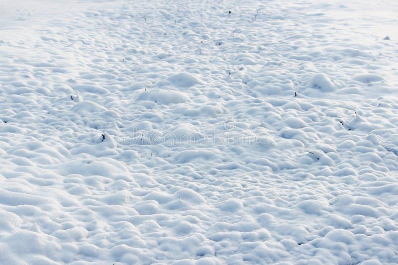 textur av vit snö som små drivor som täckte den grävde jorden arkivbild